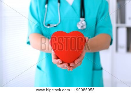 Female surgeon doctor with stethoscope holding heart