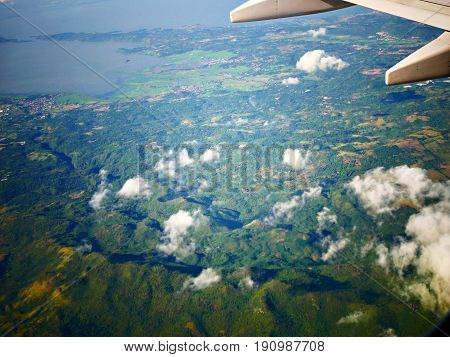 Aerial view of Luzon province, Philippines View from an airplane window showing the green lushness of Luzon province with white cotton clouds