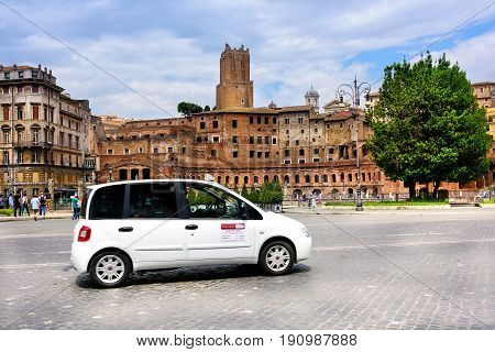 Rome Italy - June 10 2016: Taxi drives down street busy with pedestrians and lined with ancient Roman architecure.