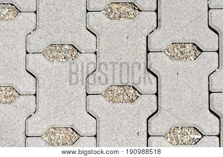 Modern cement paving bricks laid out on an exterior patio or sidewalk with areas filled with gravel forming a pattern