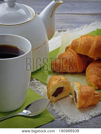 Closeup teapot and cereal croissant on the vintage wooden table. Healthy cereal croissant. Sliced croissant with chocolate. Close-up. Lunch.