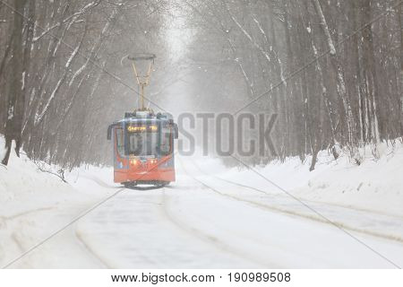 MOSCOW - JAN 15, 2017: Tram number four moves along the rails among the snowy trees on the route Metro Boulevard Rokossovsky