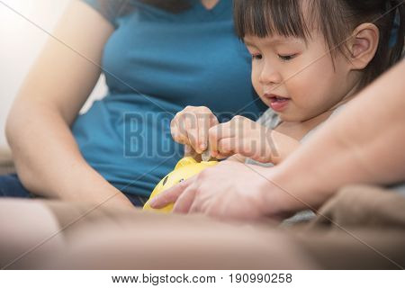 Closeup Asian little kid girl putting coin into yellow piggy bank with family.