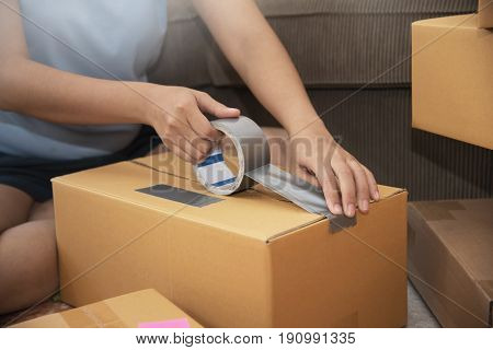 Close up of Asian woman hands packing cardboard box. Moving house concept.