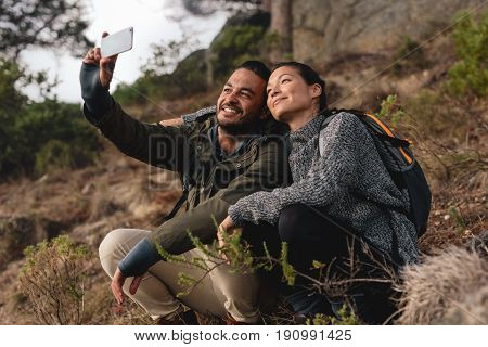 Couple Sitting On Mountain Trail And Taking Selfie