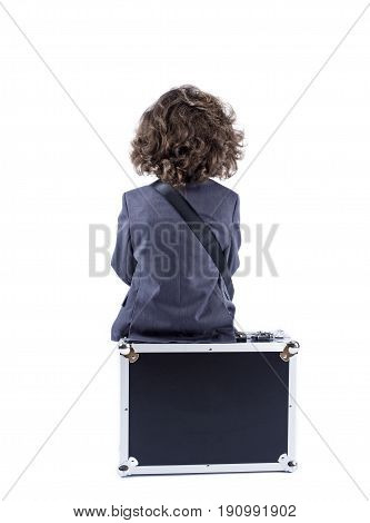 Little Curly-haired Boy Sitting On The Black Suitcase With His Back To The Camera Isolated On White