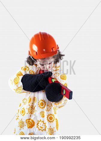 Funny Curly-haired Boy Builder In A Raincoat Holding A Building Level.foreman In An Orange Construct