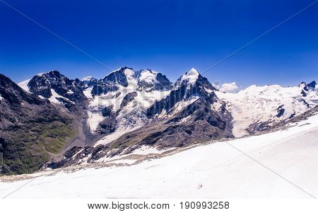Snowy peaks of the Bernina range mountain tops under a clear blue sky seen from Corvatsch at 3303m. Corvatsch Engadin Grisons Switzerland