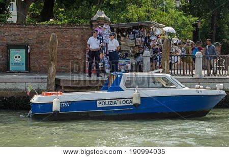 VENICE ITALY - JUNE 13 2017: Two police officers operating a speed trap beside a busy stall selling tourist souvenirs on the Grand Canal in Venice.