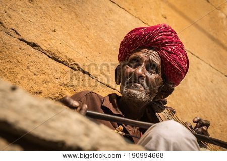 Indian senior plays traditional musical instrument in Jaisalmer Fort, Rajasthan, India