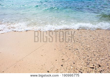 Seaside view with sand beach and sea wave. Turquoise blue tropical sea lagoon for perfect vacation. Summer paradise banner template. Tropic seaside photo for background. Honeymoon holiday destination