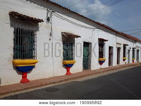 A street in Mompox with windows painted in the colours of the Colombian flag