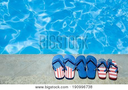 Summer background with flip flops of American flag colors and pattern near the swimming pool