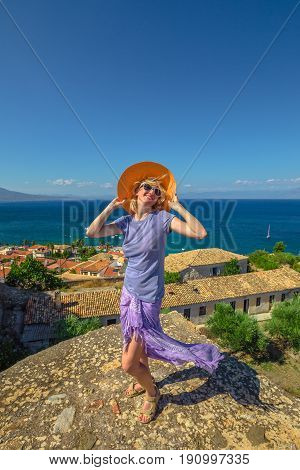 Happy tourist vacation woman with sarong and sun hat enjoying on roof of Agios Ioannis Monastery inside Koroni Fortress in Peloponnese, Greece, Europe. Happiness travel holidays lifestyle concept.