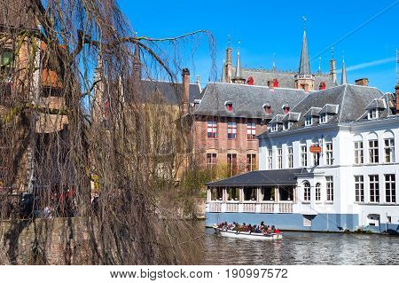 Bruges, Belgium - April 10, 2016: Scenic cityscape with medieval houses and canal in Brugge, Belgium