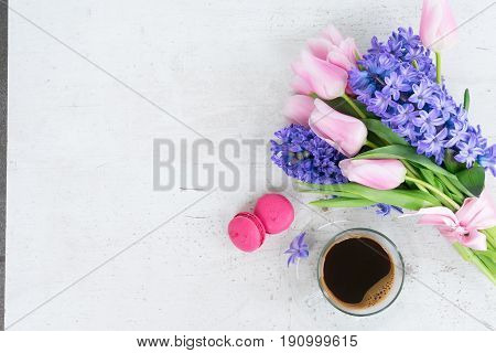 tulips and hyacinths fresh flowers with cup of coffee, holiday breakfast, copy space on white wooden background