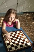 Little girl playing draughts board outdoor (camping) in the sunny summer day. The touristic tent in background. Education summer active recreation and touristic concept. poster