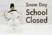 School canceled message A snowman with text Snow Day School Closed on weathered wood poster