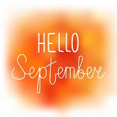 Hello september elegant greeting card with hand-written curled line lettering on blurred wet orange and yellow paint stains background. Mesh tool watercolor imitation with text greeting to september. poster