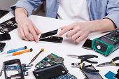 Repairman disassembling smartphone for inspecting. Technician fixing broken phone, electronics repair service poster
