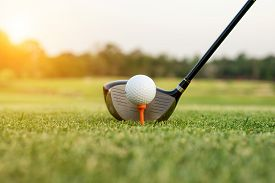 Golf club and ball in grass with sunlight. Close up at golf club and golf ball.