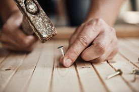 Carpenter with hammer and nails repairing part of furniture on the floor. Concept of construction and woodwork.