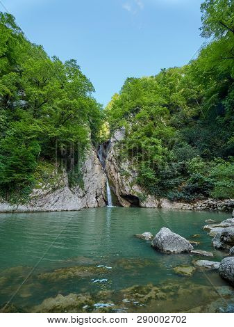 A High Waterfall Falls From A Cliff Into A Clear Lake. The Waterfall Is Surrounded By Green Forest.