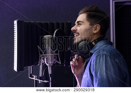Young Singer With Microphone Recording Song In Studio