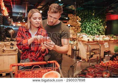 Young Couple In Grocery Store. They Stand Together And Read Text On Berries Plate. Trolley With Groc