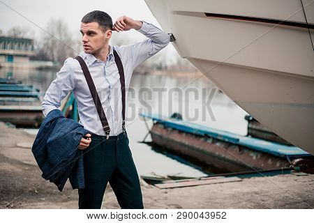 Handsome Young Male Businessman Stands In A Jacket On The Quay At The Boat Station