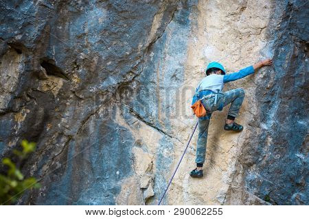 A Child Climber Climbs On A Rock. The Boy In The Helmet Climbs Up The Cliff. Strong Kid Overcomes A