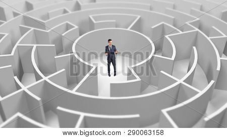 Young businessman standing in a middle of a 3d round maze