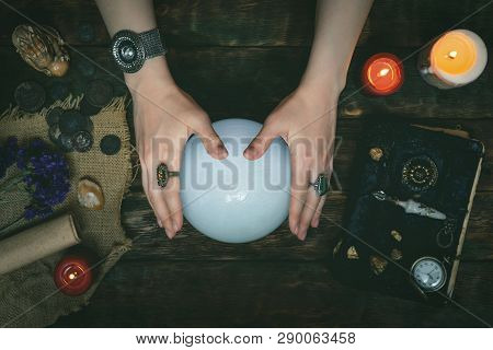 Future Teller And A Crystal Ball Is Reading A Future On A Magic Table Background.
