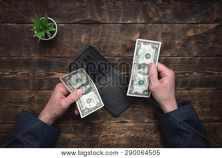 Business man is holding in hands a empty wallet with few dollars. Tight of money. Lack of money. Financial problems. Bankrupt. Pay the bill concept. poster