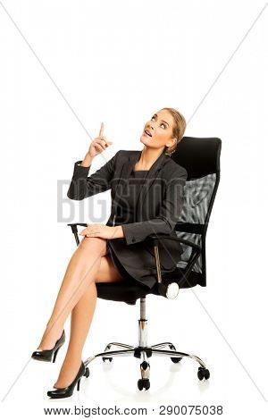 Full length of business woman sitting on chair and presenting copy space.