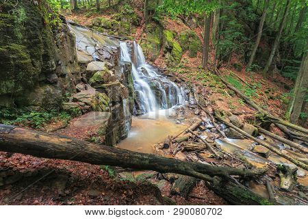 Waterfall On The River Among Forest. Fallen Trees Among Huge Mossy Boulders. Spring Freshness In The
