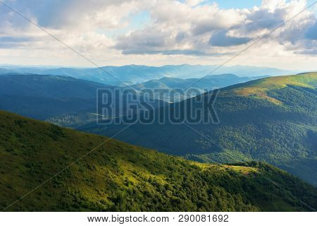 Beautiful Mountain Landscape In Summer Afternoon. Green Alpine Meadows And Forested Hills. Ridge In