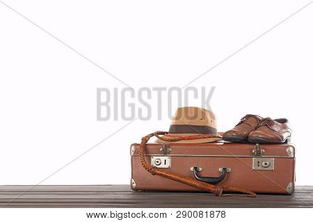 Travel and adventure concept. Vintage brown suitcase with fedora hat, bullwhip and shoes against white isolated background. poster