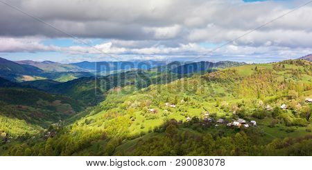 Countryside Of Panorama In Springtime. Village On The Hillside, Mountain Ridge In The Distance. Sunn