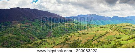 Countryside Of Panorama In Springtime. Rural Fields On Hillside, Mountain Ridge In The Distance. Ove