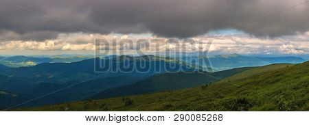 Panorama Of Grassy Alpine Meadow In Mountains. Overcast Rainy Weather. Rows Of Divide Ridges In The