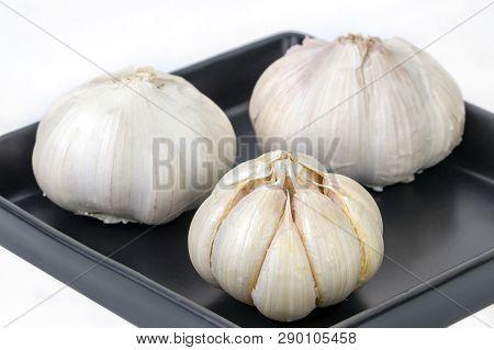 Raw And Peeled Garlic On Balck Dish On White Background