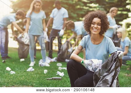 Volunteering, Charity And Ecology Concept. Friendly African-american Woman Volunteer With Friends Cl