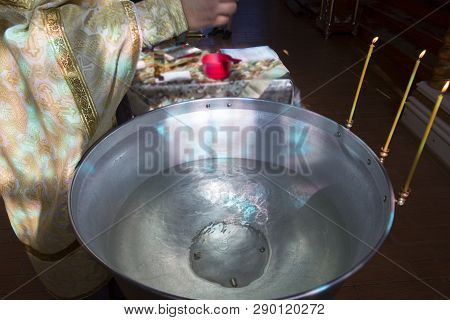 The Rite Of Baptism. Priest Prepare To Baptize The Child. Font For Taking Faith