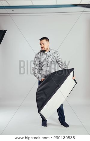 Man Works In A Photo Studio With Light, An Assistant Assistant Director Softbox Photo Session Creati