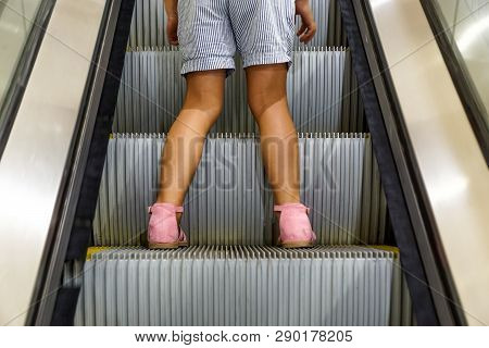 Young Female Kid On A Moving Escalator . Do Not Let A Child Go Alone On An Escalator Concept