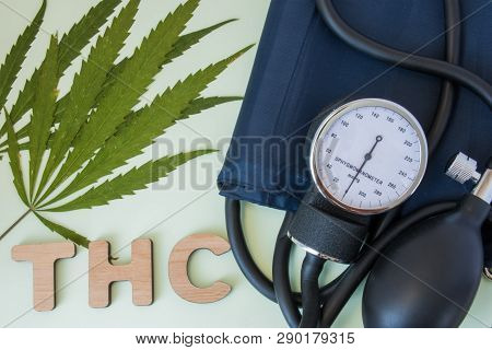 Smoking Cannabis And High Low Blood Pressure Photo Concept. Sphygmomanometer Is Near Two Leaf Of Can