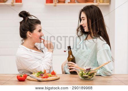 Two Young Females Making Salad At Kitchen