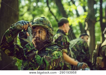Young Soldier Man With Beard On Grime Serious Face In Ar Y Ammunition And Helmet Holding Camera In H