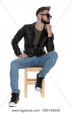 man in black jacket and blue jeans sitting on chair thinking while being goofy on white background
